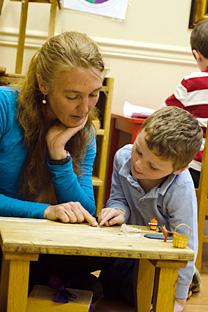 Teacher Helping Student at Divinum Auxilium Academy