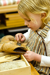 Child cleans Boot to improve sensorial learning at Divinum Auxilium Academy